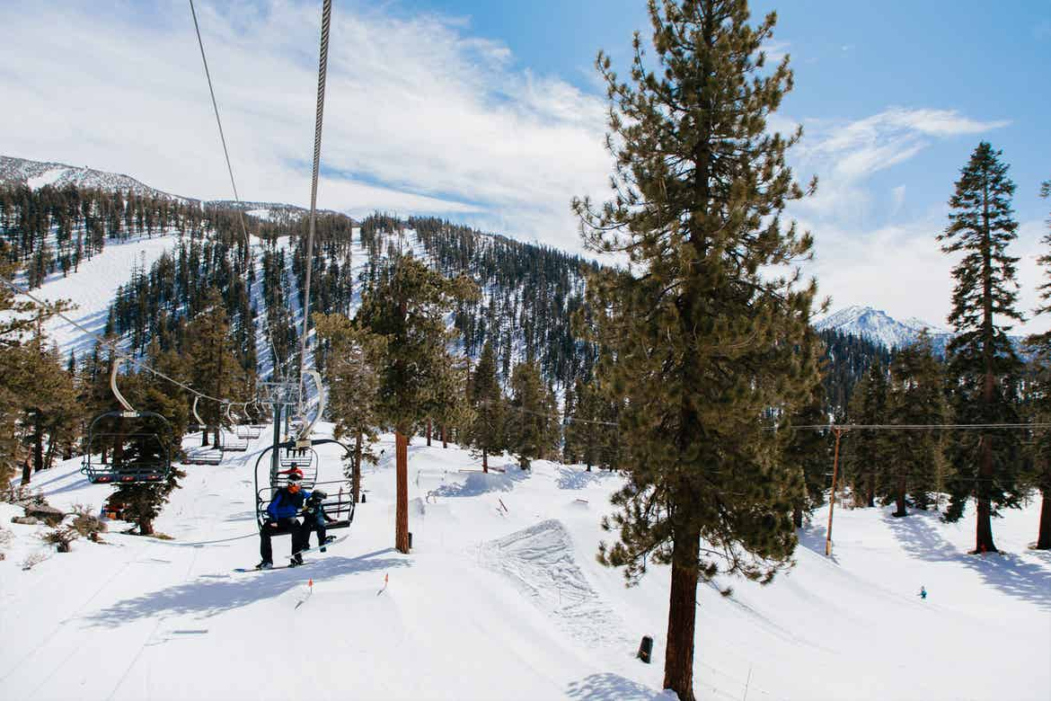 The chair lift at our Tahoe Ridge resort with two guests in ski gear.