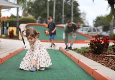 Young girl picking up a golf ball at a miniature golf course