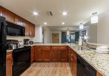 Full kitchen with refrigerator, microwave, stove, dishwasher, and sink in a two-bedroom villa at Scottsdale Resort