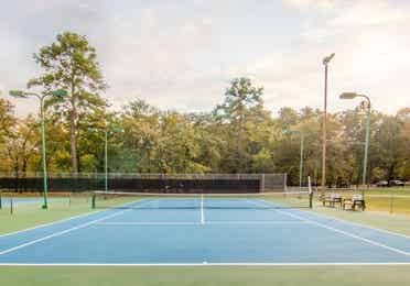 Outdoor tennis court surrounded by trees at Holly Lake Resort in Texas.