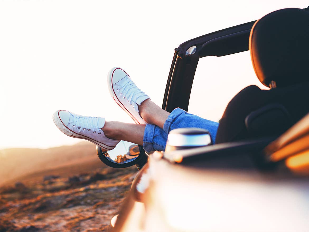 A woman wearing white sneakers sticks her feet out of the convertible car near a beachfront as the sun sets.