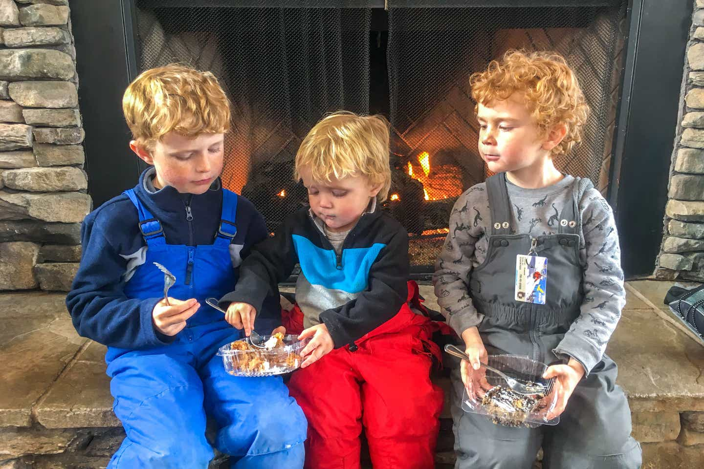 Jessica's three sons sit on the hearth with snowpants enjoying a delectable carrot cake.