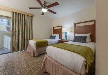 Guest bedroom with two twin beds and access to balcony in a three-bedroom villa at Scottsdale Resort