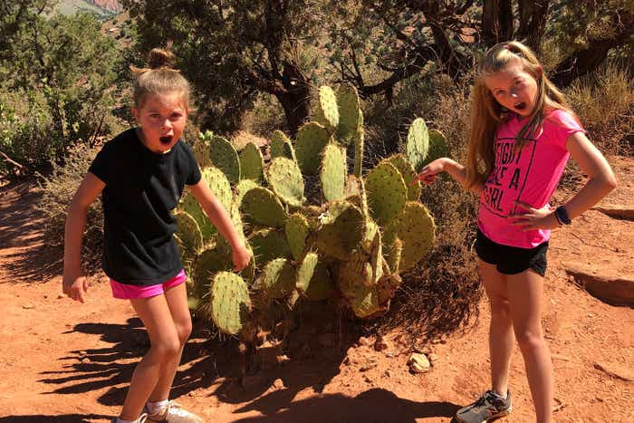 Kyler (left) and Kyndall (right) pose in front of a cacti at Zion National Park.