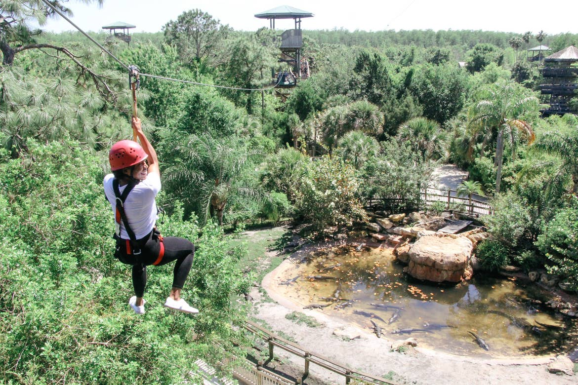 Featured Contributor, Monet, wears a red safety helmet and harness while zip lining over a gator enclosure at Gatorland.