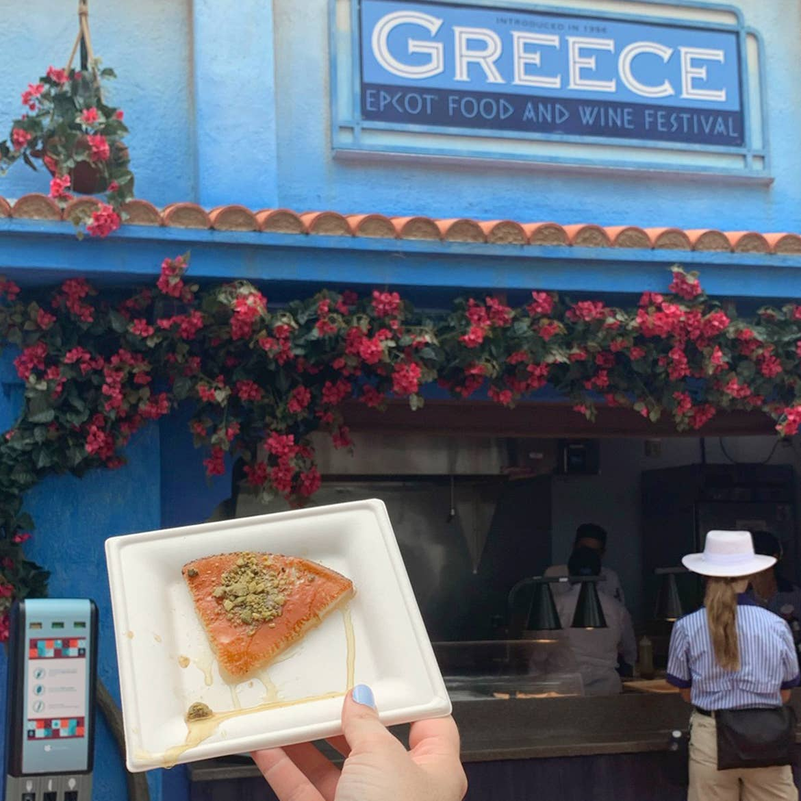 A hand holds a white, square plate containing a Griddled Cheese slice with Pistachios and Honey at the Greece kiosk at Epcot.