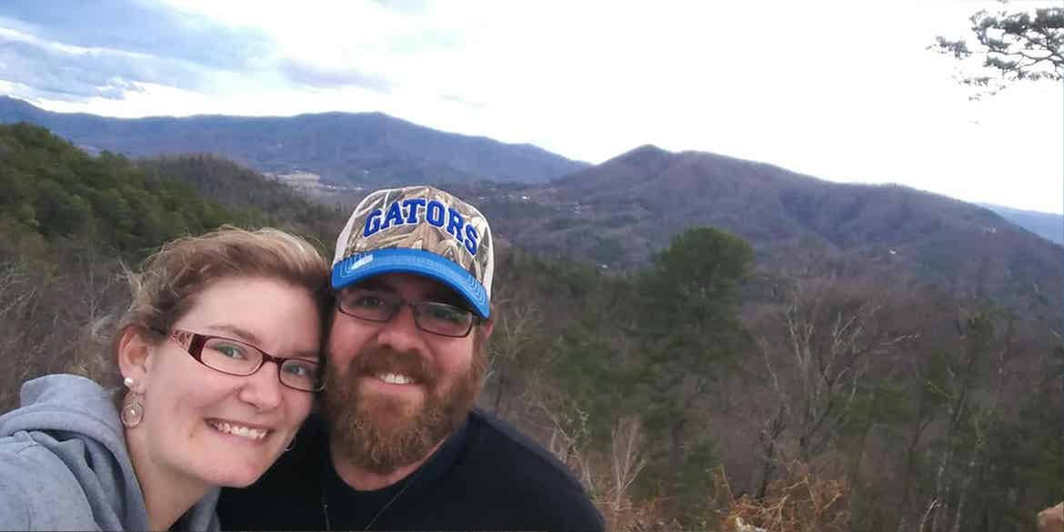 Becca and her husband taking a selfie in front of the mountains