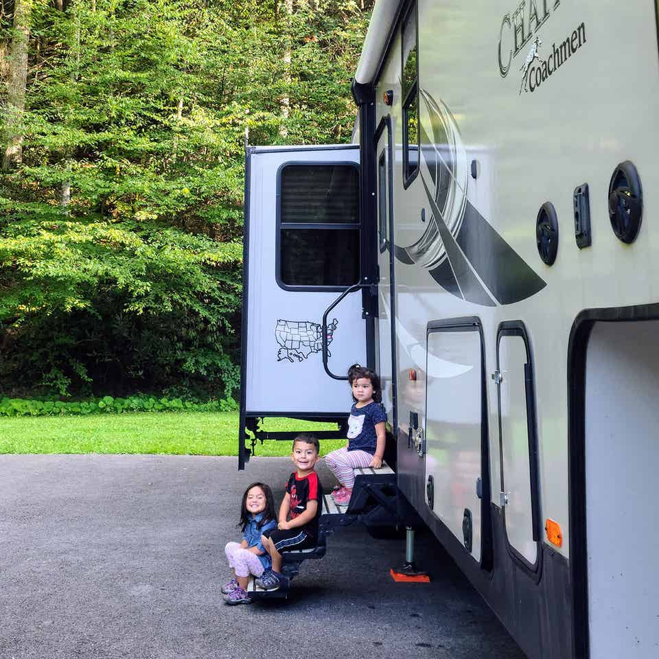 Angelica's children sitting on the steps of their RV.