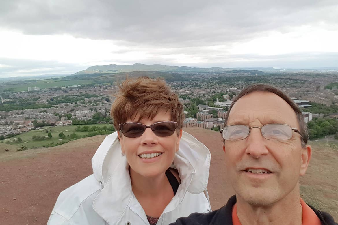 A caucasian male (right) wearing a navy windbreaker and a caucasian woman wearing a white windbreaker jacket stand on a clay hill overlooking Arthur's Seat in Edinburgh, Scotland.