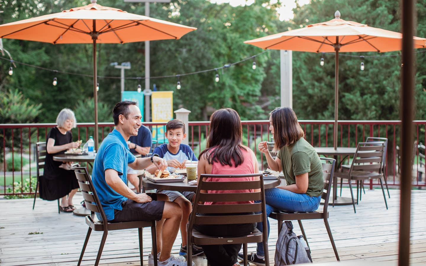 Family of four eating on patio of Grill at Villages Resort in Flint, Texas.