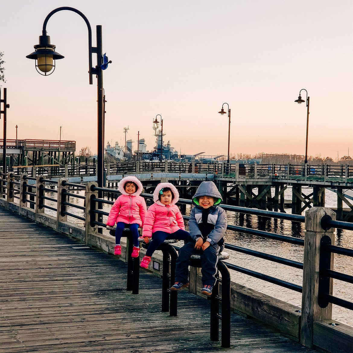 Three Asian Pacific Islander toddlers (left to right: Two girls and a boy) wear pink and blue winter coats while seated on safety railing near a dock for battleships.
