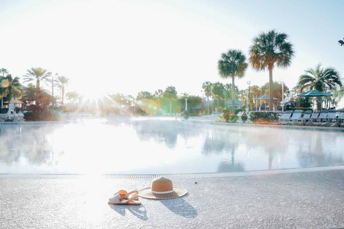 A hat and sandals lying next to the zero-entry pool in West Village at Orange Lake Resort