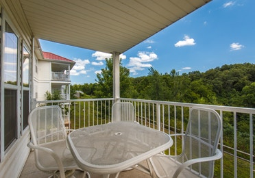 Balcony with table and chairs in a two-bedroom ambassador villa at the Holiday Hills Resort in Branson Missouri.