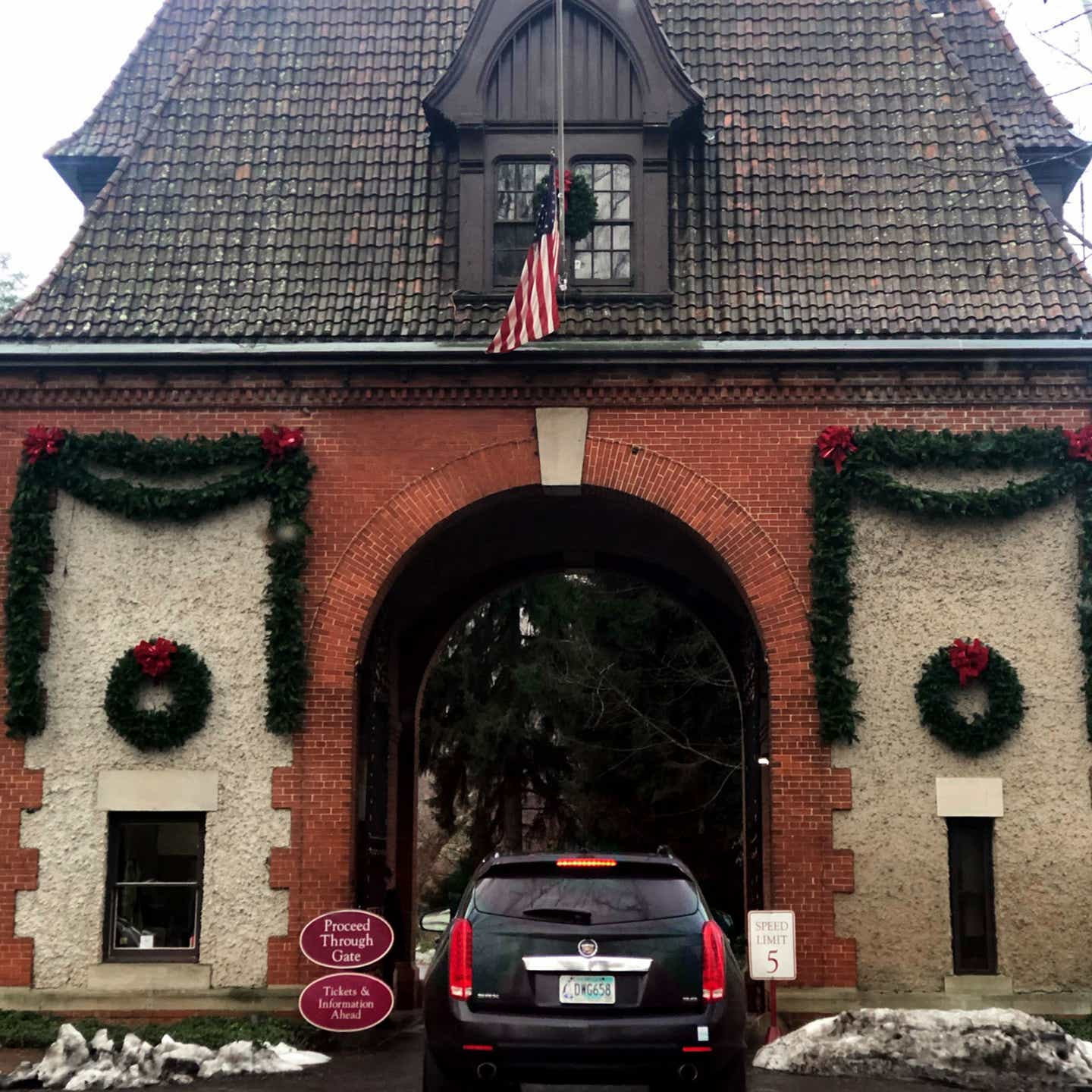 The exterior of the Biltmore Estate entrance under a cloudy sky with lush green garland decorating the facade as a black SUV enters.