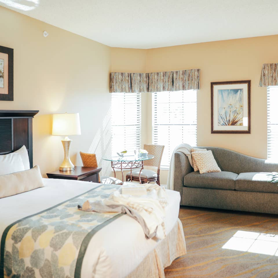 Bedroom with bed, couch, and three windows in a villa in East Village at Orange Lake Resort near Orlando, Florida
