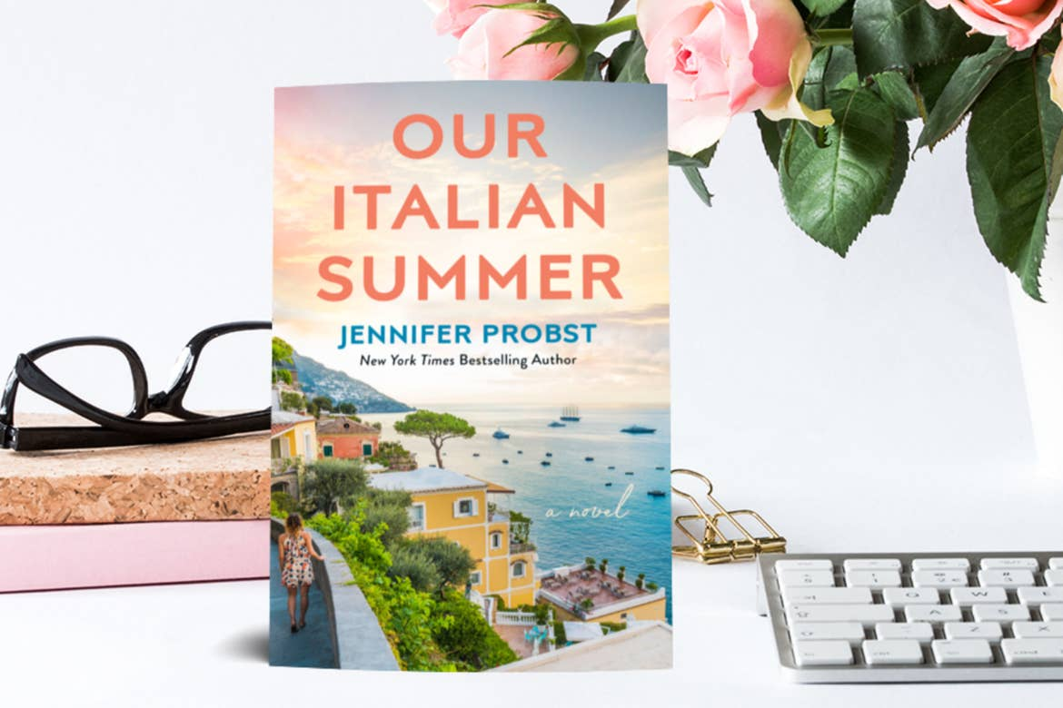 A book stands on display in front of a white background with black glasses, a keyboard, and some flowers that read, 'Our Italian Summer, Jennifer Probst, New York Times Best-Selling Author.'