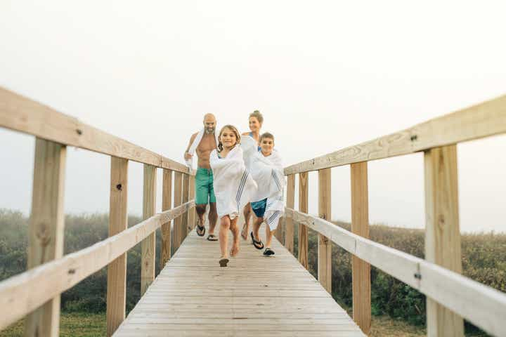 Family running on beach pier