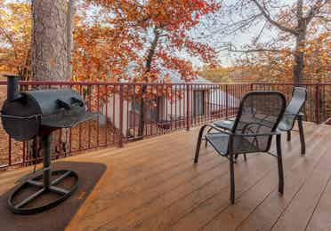 Furnished balcony with table, two chairs, and a grill in a two-bedroom cabin at Ozark Mountain Resort in Kimberling City, Missouri