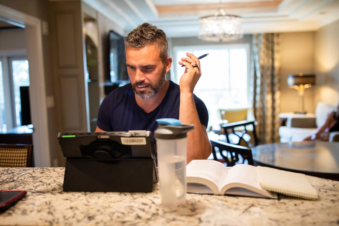 Brenda's husband, Isaiah, sits at the kitchen countertop with his laptop as he works remotely.