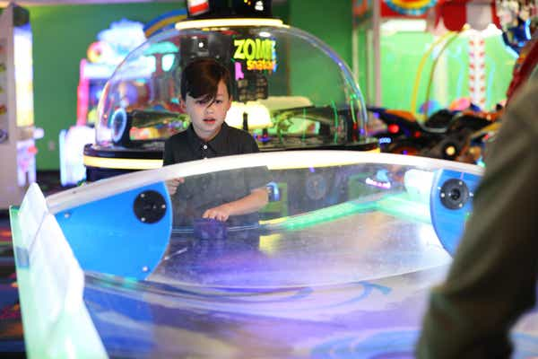 Young boy playing arcade game at Orange Lake Resort near Orlando, Florida