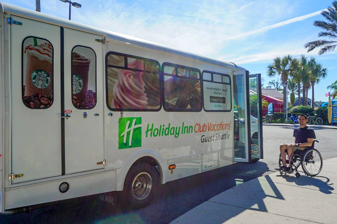 Author, Danny Pitaluga (right) sits in his wheelchair wearing a black shirt and khaki shorts next to a white hotel shuttle bus that reads 'Holiday Inn Club Vacations.'