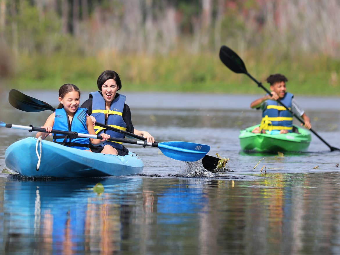 A woman (middle) and two tweens (left and right) kayak in a lake.