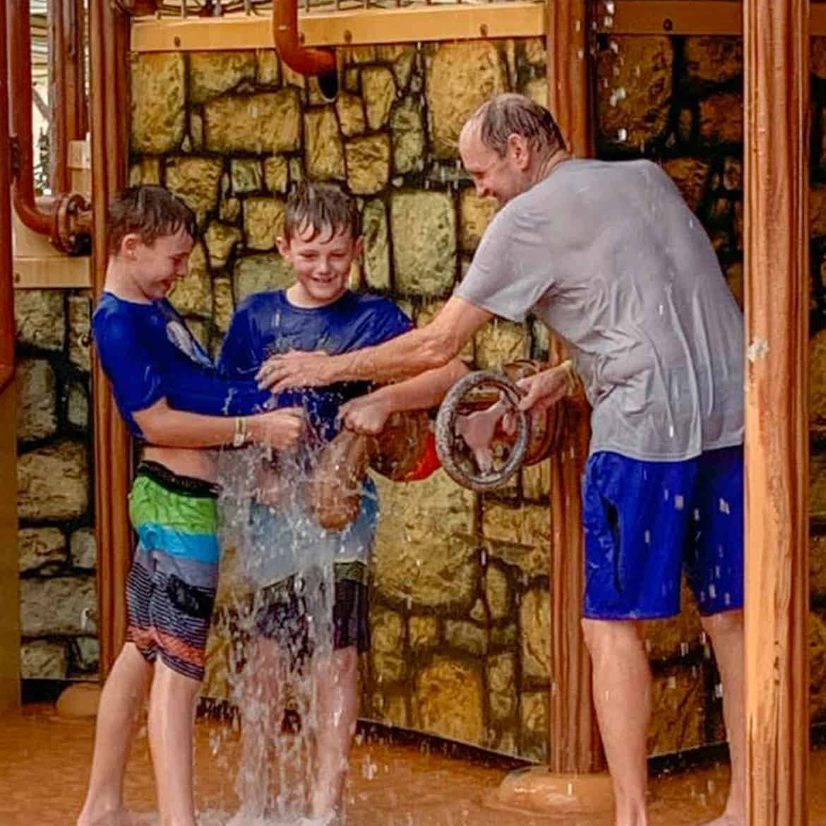 Author, Amanda Nall's father (right) and sons (left) play in the water park splash station.