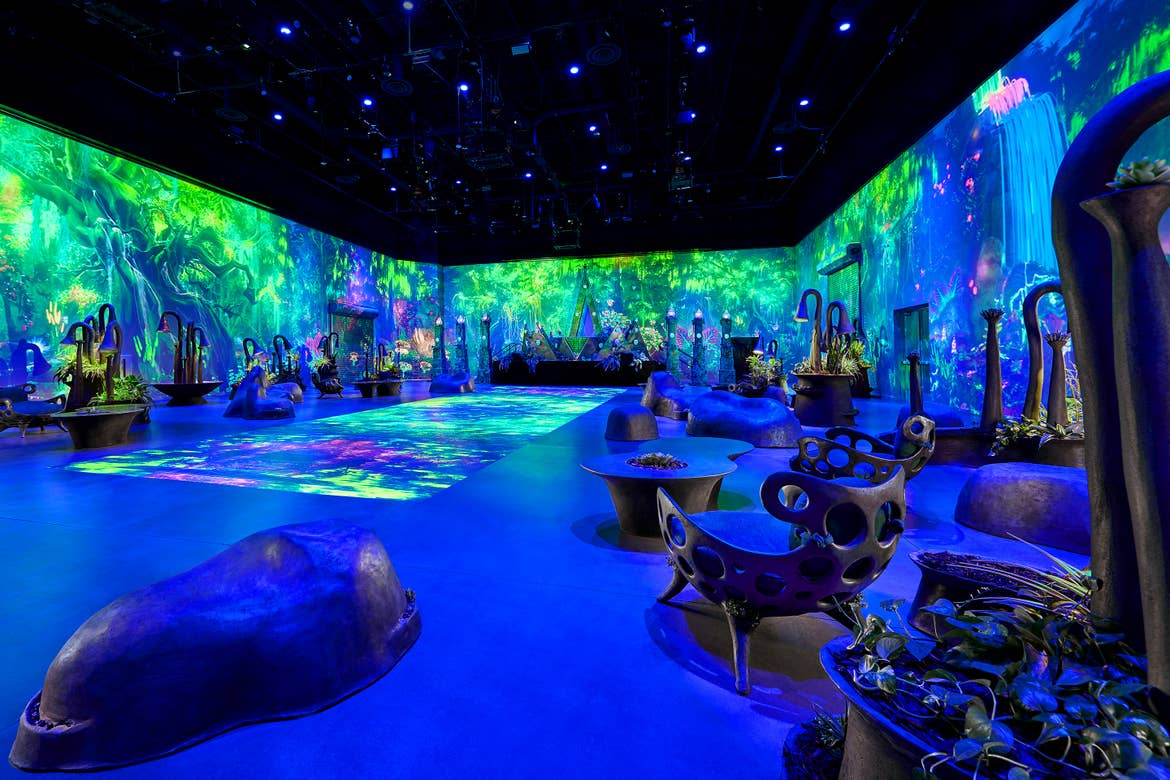 An interior space with all four walls covered in LED panels simulating garden backdrops.