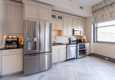 Full kitchen with fridge, dishwasher, microwave and oven in a one-bedroom Signature Collection villa at New Orleans Resort in Louisiana.