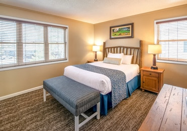 Bedroom with bench, end tables, and two large windows in a one bedroom villa at Oak n' Spruce Resort in South Lee, Massachusetts