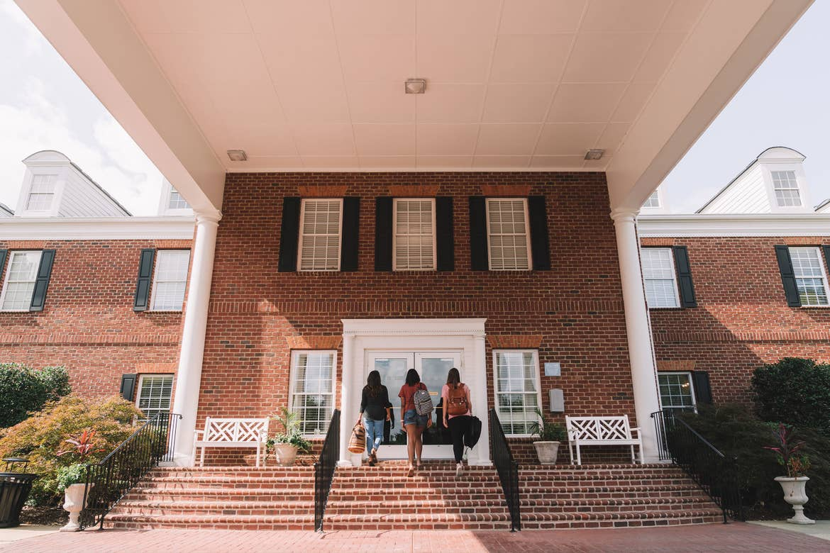 Three female guests carry their luggage into the lobby from the exterior of our Williamsburg resort in Williamsburg, Virginia.