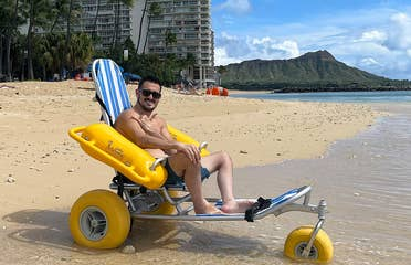 Featured Contributor, Danny Pitaluga, wears sunglasses and swim trunks while sitting in a yellow beach wheelchair on the sand as waves roll in.