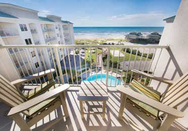 Balcony with two chairs overlooking the resort pool and beach in a Signature two-bedroom villa at Galveston Beach Resort