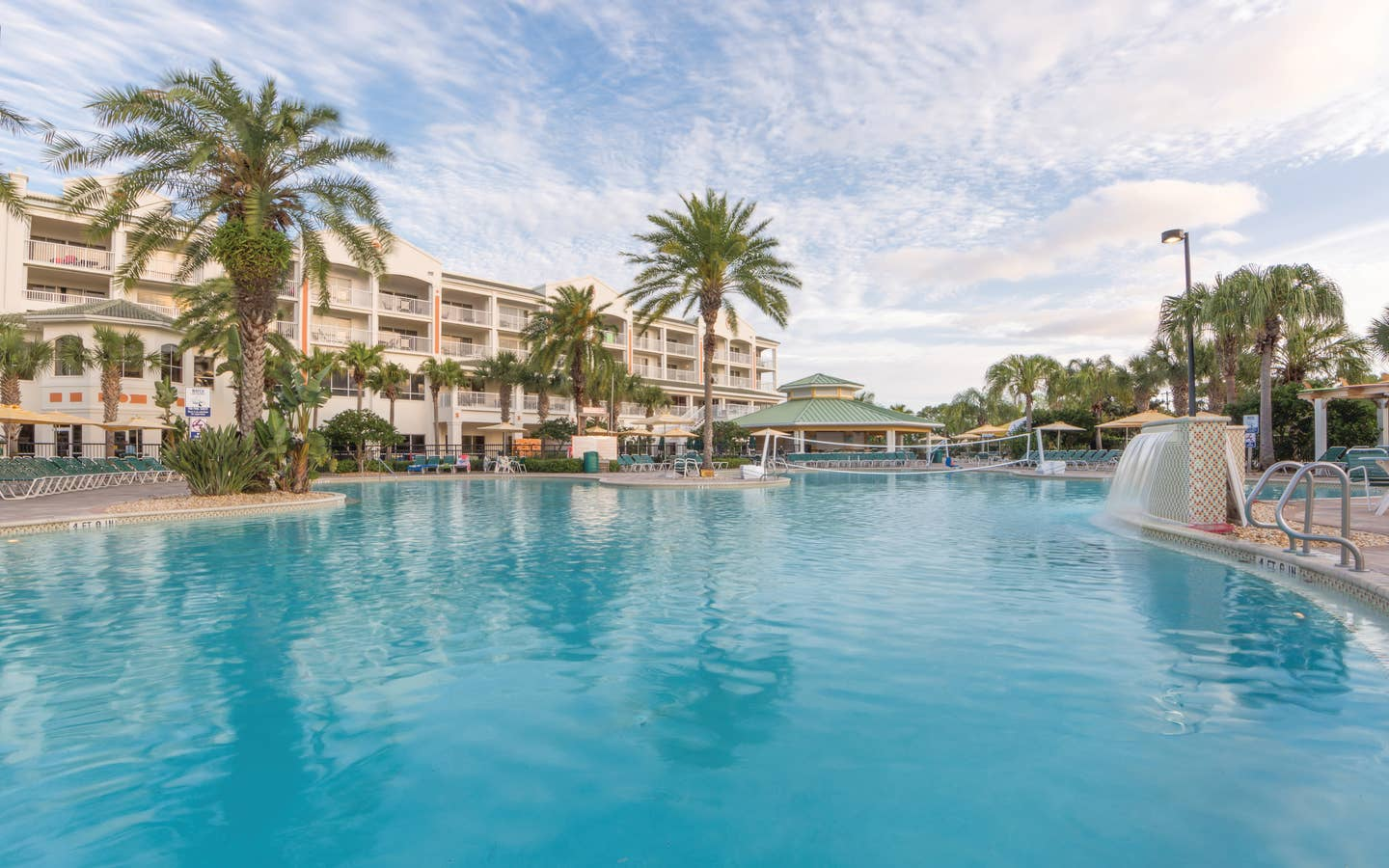 Outdoor pool with waterfall, volleyball net, beach chairs, and umbrellas at Cape Canaveral Beach Resort.