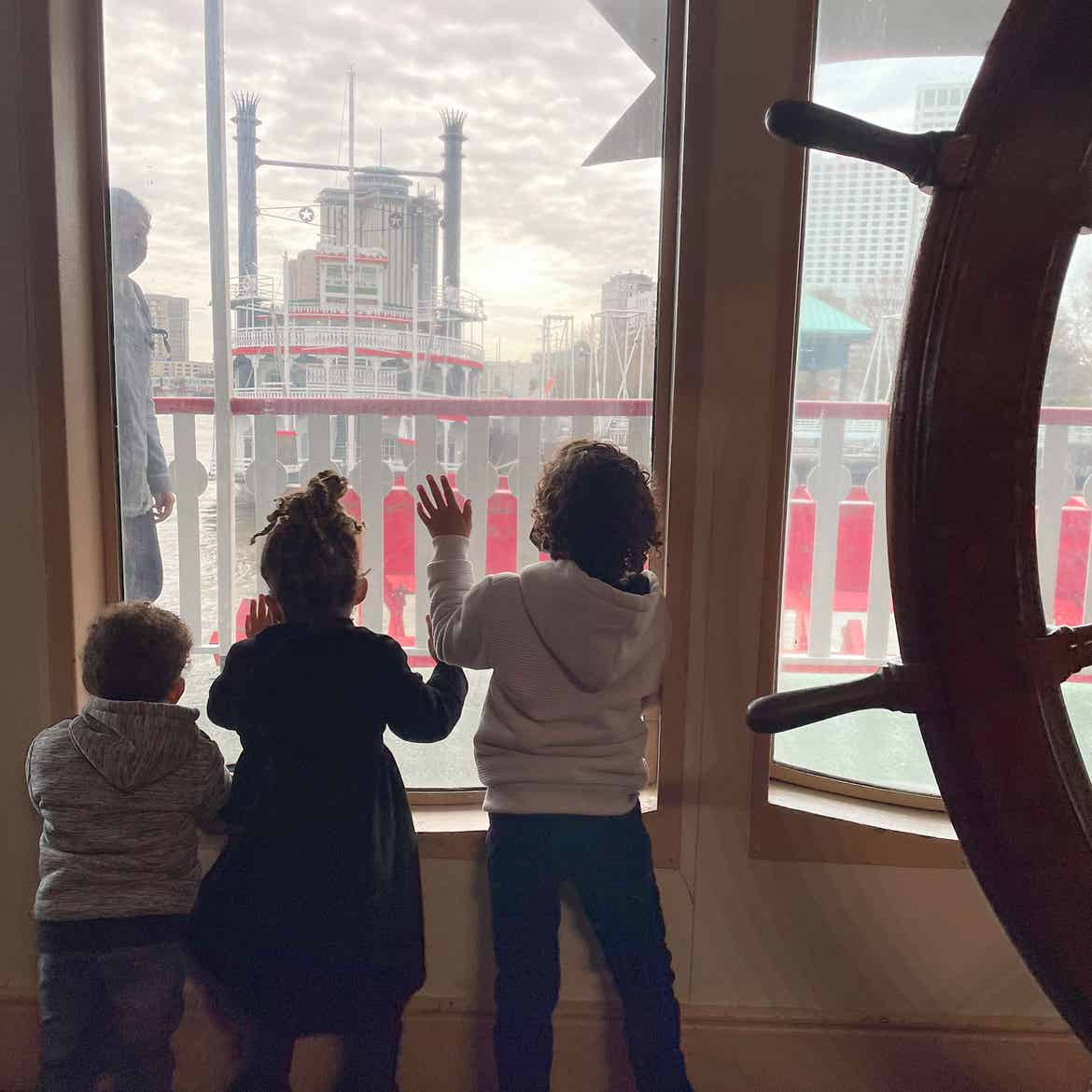 Featured Contributor, Sally Butan of @butanclan's children, Alston (left), Alissa (middle), and Alex (right) look out of a window on the Steamboat Natchez of the Mississippi River of New Orleans, Louisiana.