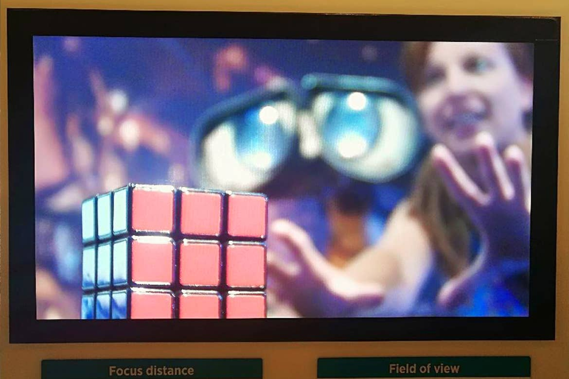 A monitor shows a woman standing next to Pixar's Wall-E reaching out for a Rubik's Cube.