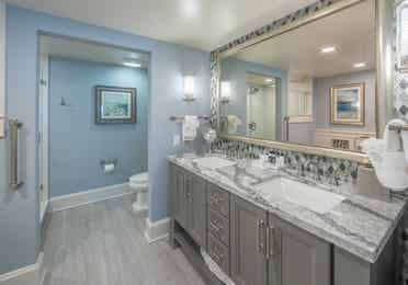 Bathroom with double sinks and a large mirror in a two-bedroom Signature villa at Cape Canaveral Beach Resort