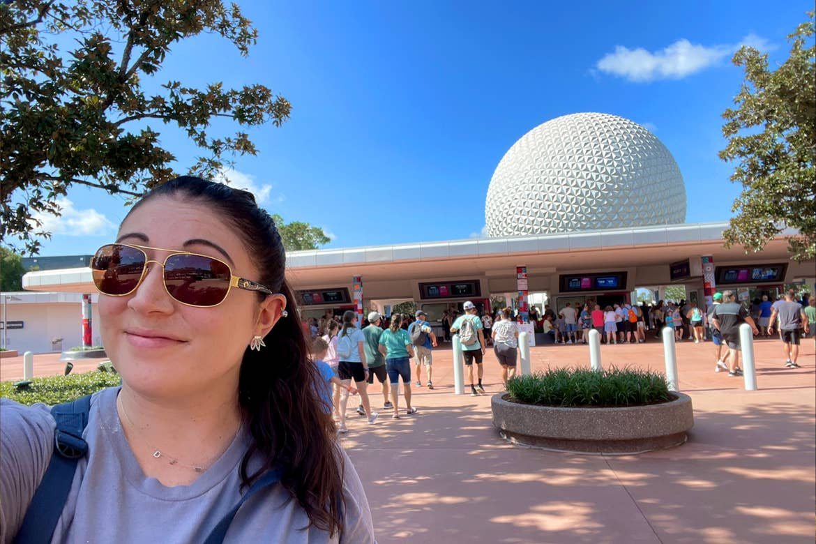 A woman wears sunglasses and t-shirt in front of the Epcot entrance.