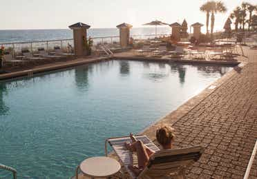 Outdoor pool with beach chairs at Panama City Beach Resort