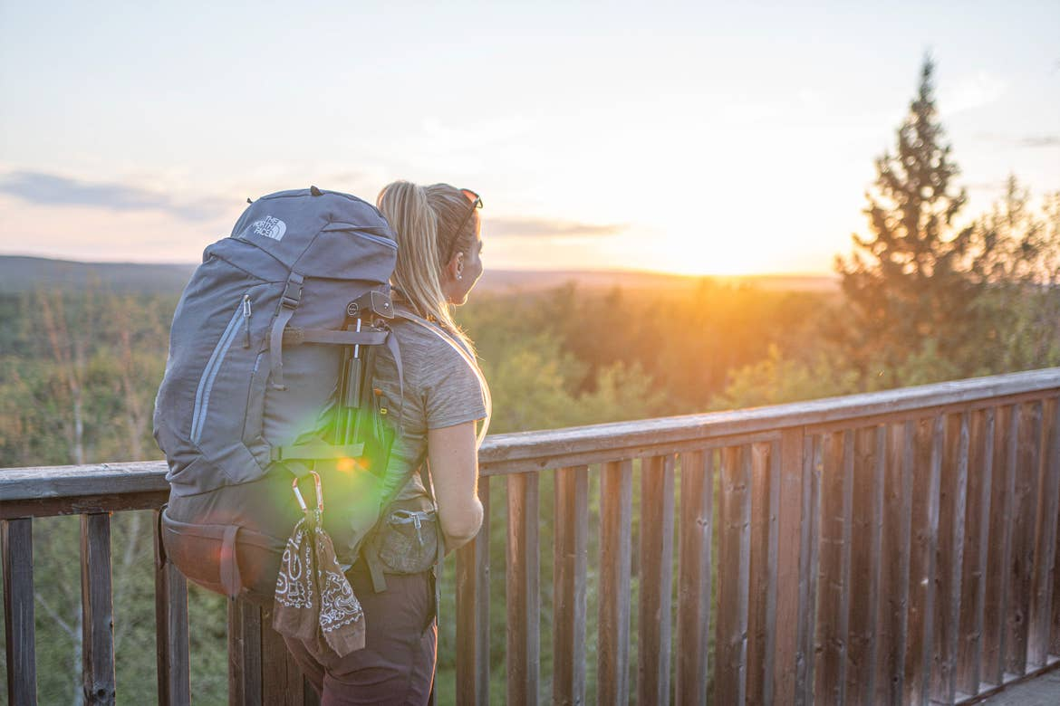 Featured Contributor, Ashlyn George, wears a backpack and watches the sunset above pine trees.