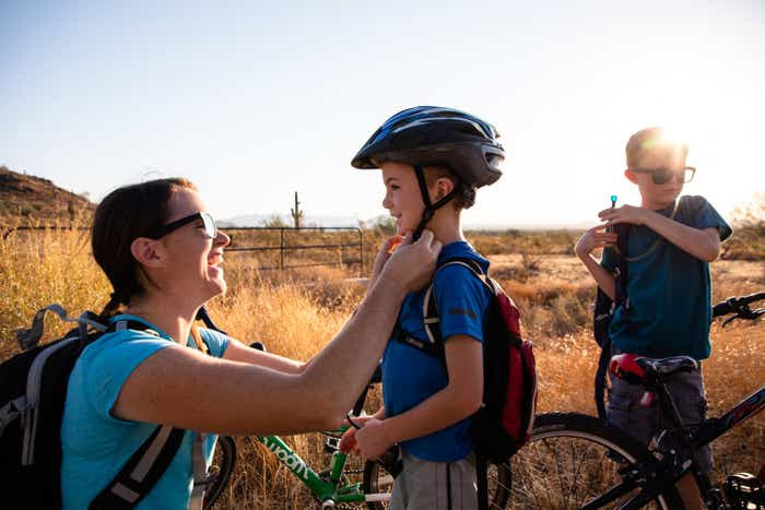 Author Jessica Averett (left) helps her son (middle) with his safety helmet as her other son (right) adjusts his Camelbak prior to riding bikes.