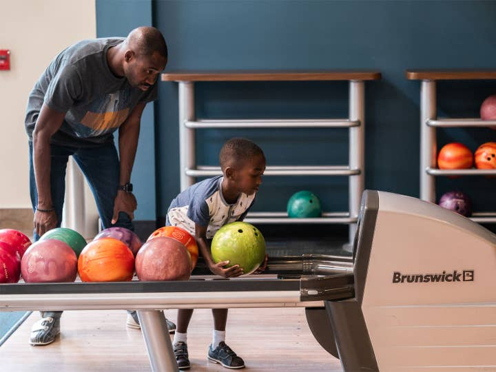 Adult and child bowling at Williamsburg Resort.