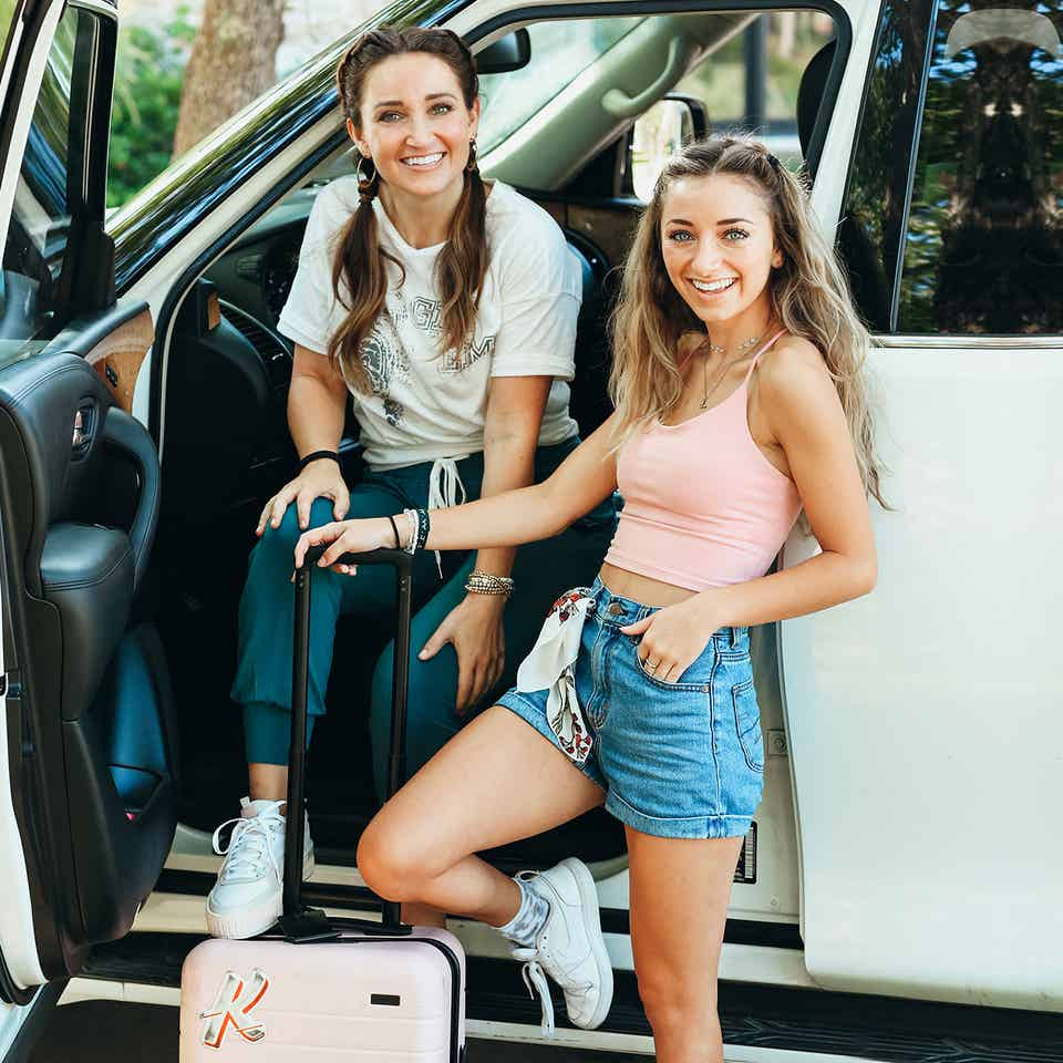 Mindy and Kamri pose near their white SUV with a pink suitcase in tow.