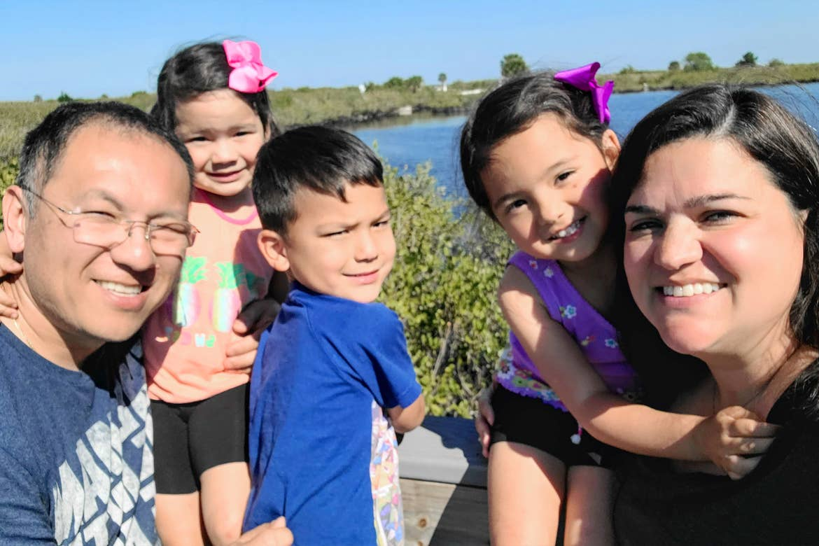 Featured Contributor, Angelica Kajiwara and her family pose outside near a lake.