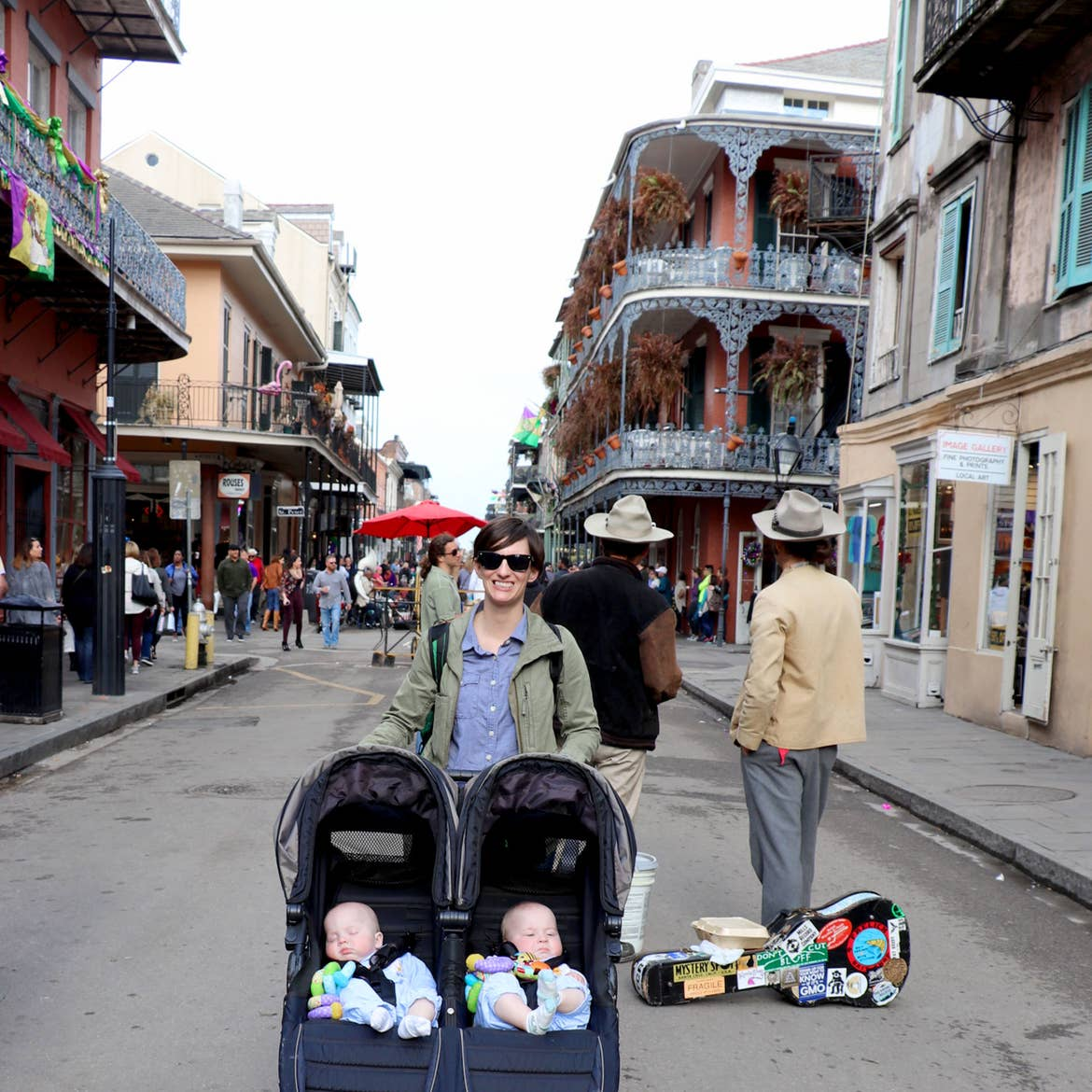 Featured Contributor, Catherine Karas's wife, stands in the middle of the French Quarter with their twin boys in a stroller.