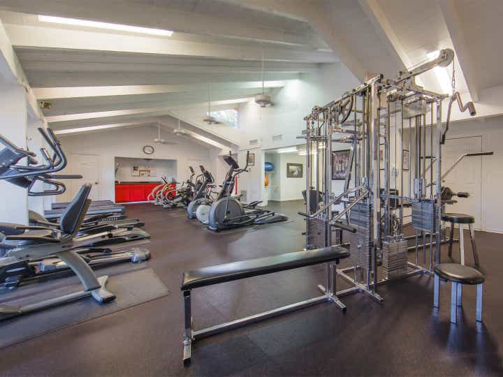 Fitness center with treadmills, weight benches and ellipticals at Holly Lake Resort in Texas.