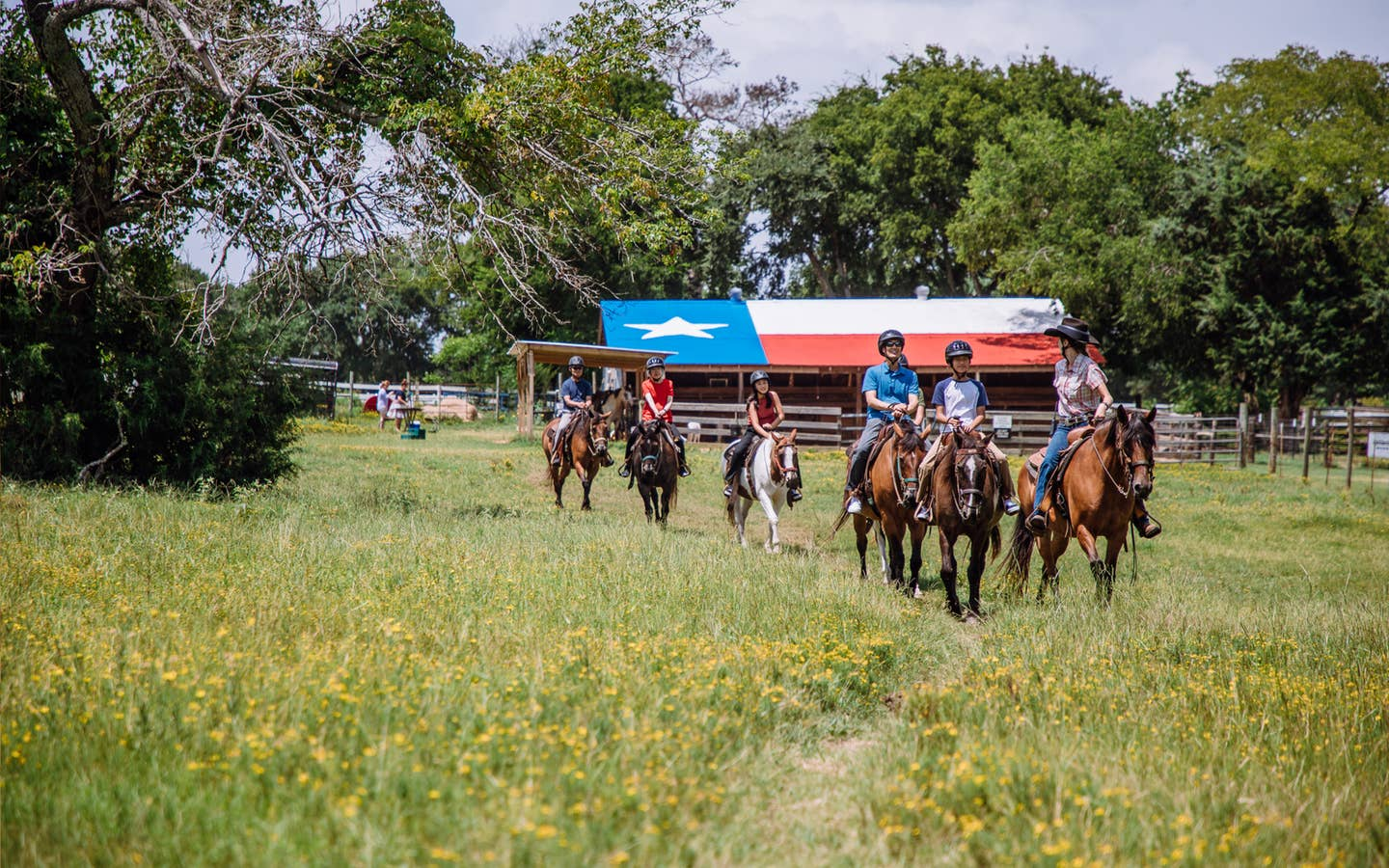 Group of guests riding horses through a field at Villages Resort in Flint, Texas.
