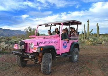 Pink jeep driving through a desert