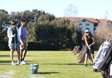 Girl holding a golf club at the driving range as two people watch.