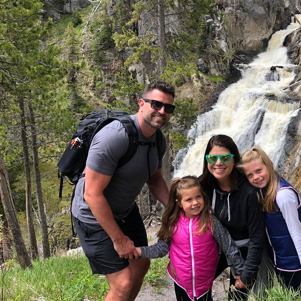 Author, Chris Johnston (middle-right), stands in front of the Mystic Falls at Yellowstone National Park with her husband, Josh (far-left), and daughters, Kyndall (far-right), and Kyler (middle-left).